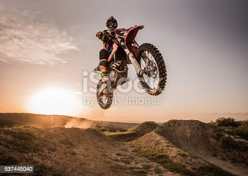 Low angle view of Enduro motocross rider jumping high up off-road at sunset. Copy space.