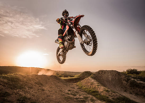 coureur de motocross performant saut en hauteur au coucher de soleil. - moto sport photos et images de collection
