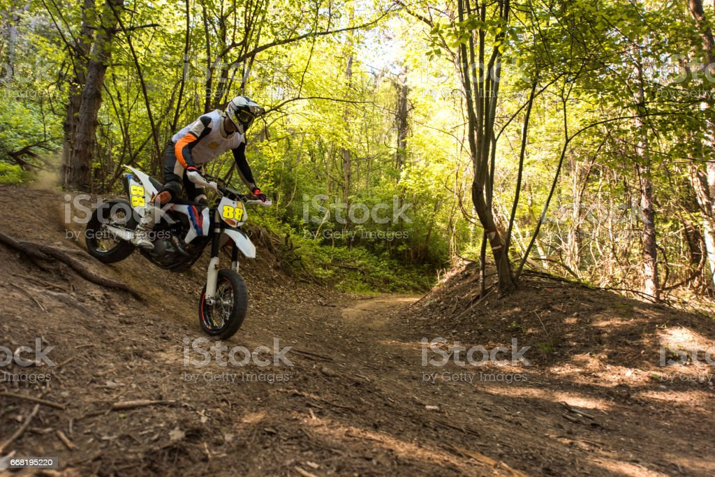 Man on dirt bike racing through the forest.