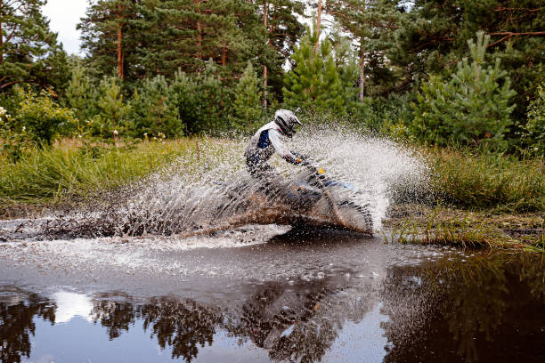 motocross rider riding a puddle in forest trail stock photo