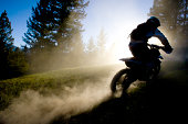 A male motocross rider hits a dusty trail in British Columbia, Canada towards the end of the day.