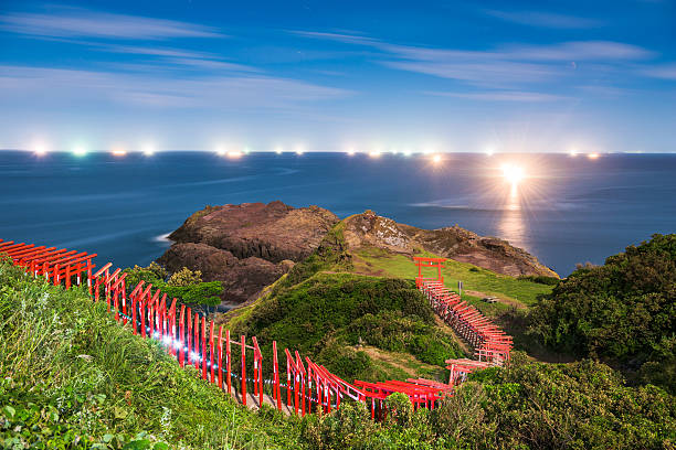 Motonosumi Shrine in Japan Nagato, Japan - August 26, 2015: Motonosumi Shrine with fishing boats on the Sea of Japan at night. The temple was established in 1955 and is known for the numerous red torii gates. torii gate stock pictures, royalty-free photos & images