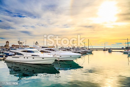 Luxury yachts at sunset. Marine dock of modern motor and sailing boats in sunshine, blue water sea, rainbow with sun. Travel and fashionable vacation.