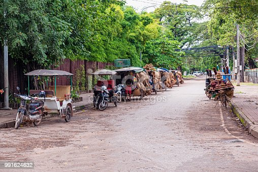 The row of motorbikes with attached carts, carrying local goods for sale. They are on the side street in Siem Reap, Cambodia.