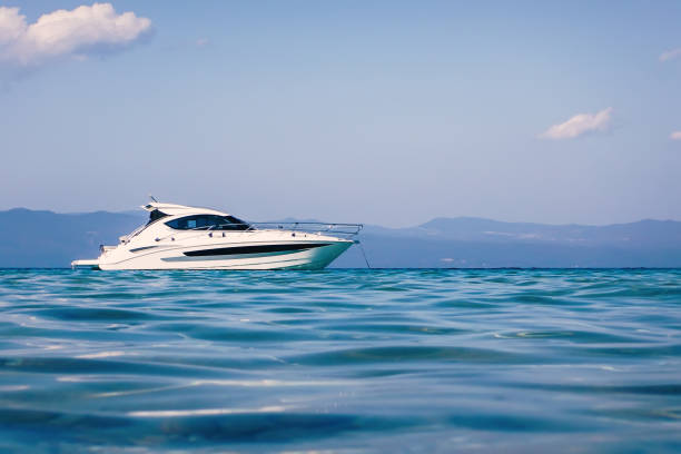 motor barco flotando en el agua clara color turquesa - yacht fotografías e imágenes de stock