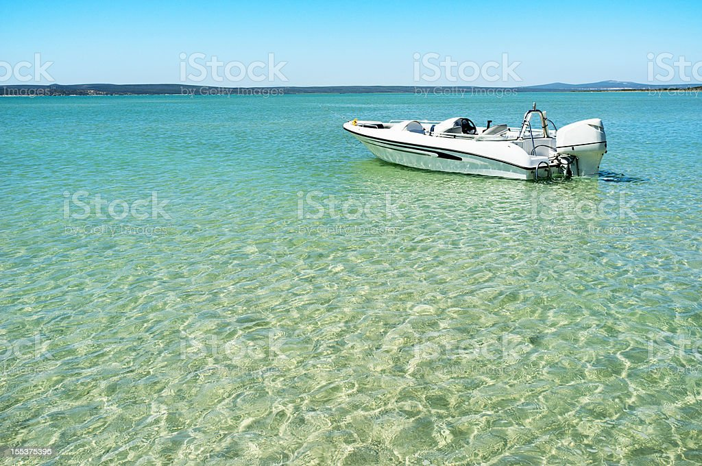 Motor boat moored in turquoise lagoon waters on summer day royalty-free stock photo
