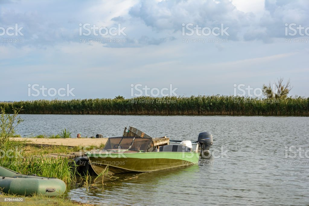 Motor boat near the wooden pier on the river on a summer day. stock photo
