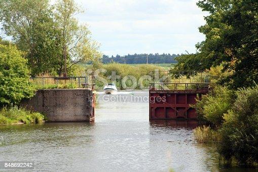 Motor boat. Open river gate. River name is Minija. Motor boat sails through the gates. Calm river