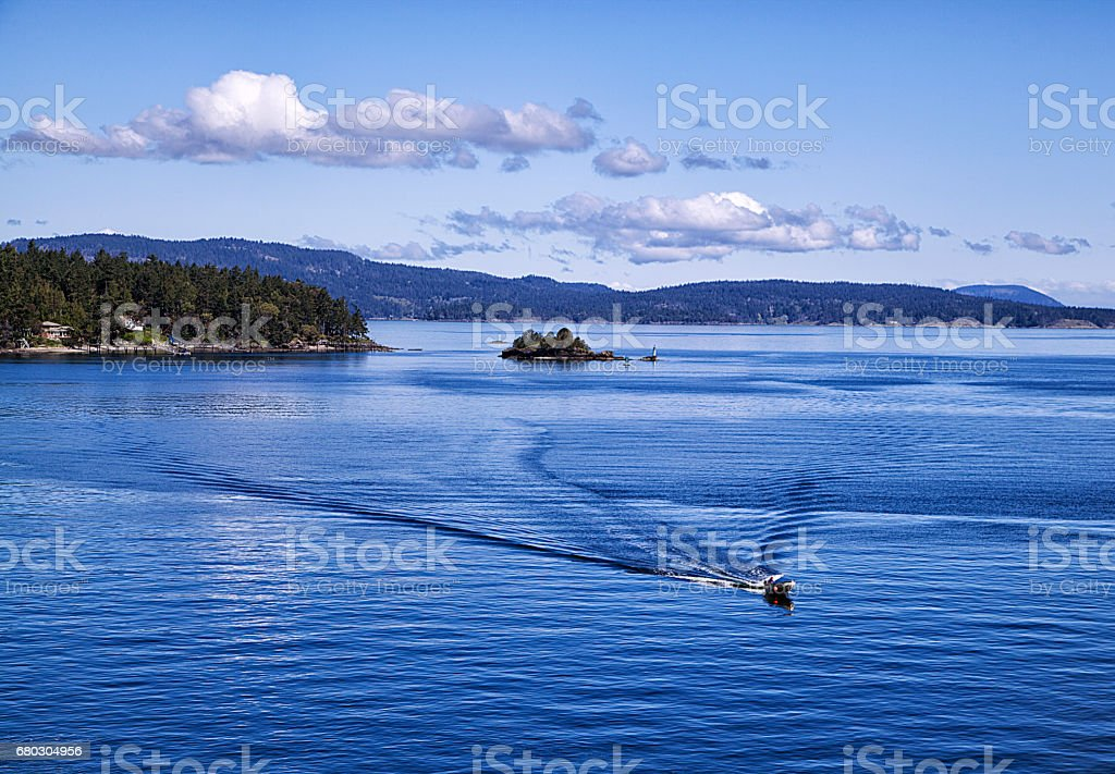 Motor boat sailing away from island at sea,Vancouver,Canada stock photo