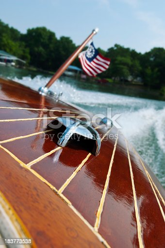 Perspective image of the stern of a vintage wooden motorboat with a patriotic flag