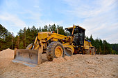 Motor Grader on road construction in forest area. Greyder leveling the sand, ground and gravel during road work. Heavy machinery and construction equipment for grading. Earthworks grader machine