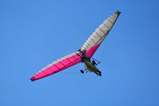 A two-seater kite flies in the clear sky