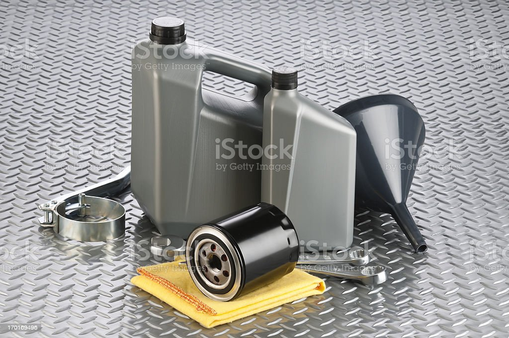 Motor oil canisters with tools on diamond plate background royalty-free stock photo