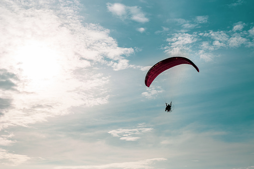 Motor paraglider flying in blue sky with white cloud in background.
