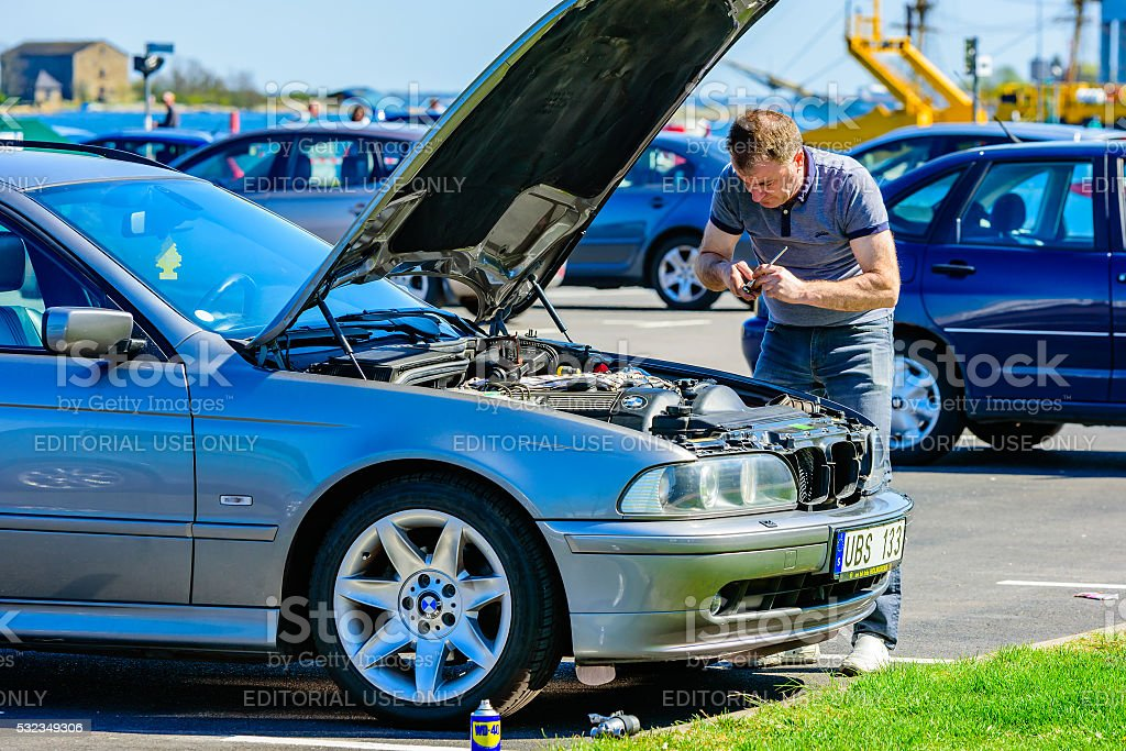 Motor problems Karlskrona, Sweden - May 3, 2016: Male person working under the hood of a 2005 BMW 525 touring on a parking lot in the harbor. Hood is open and person is using tools on the motor. Accessibility Stock Photo