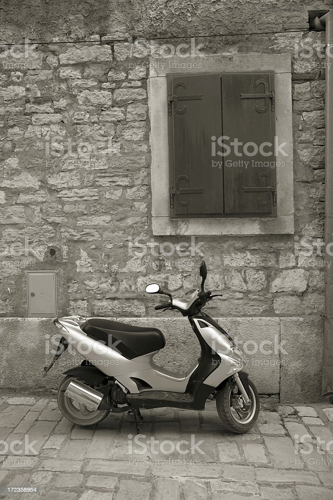 Motor Scooter parked on a cobblestone street. royalty-free stock photo