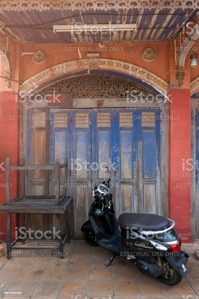 A motor scooter parking in front of classic Sino-Portuguese architectural style shophouse building at Ban Singha Tha, old historic area of Yasothon Province in the northeastern region of Thailand stock photo