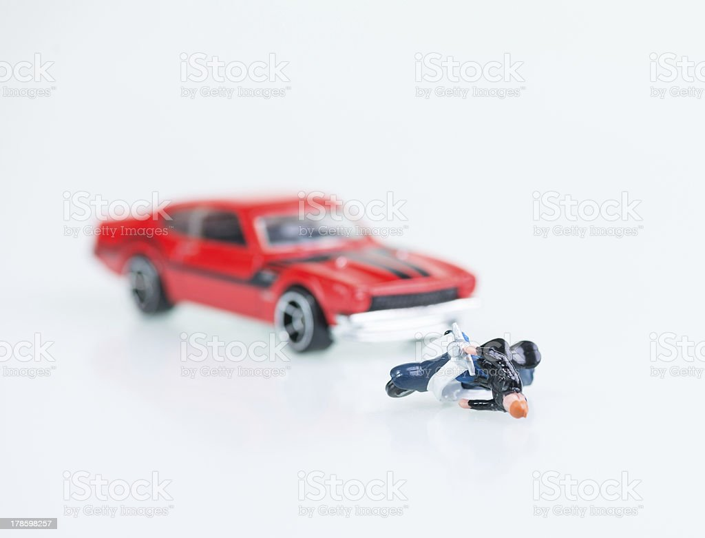 Motor vehicle collision involving a toy car and miniature motorcyclist royalty-free stock photo
