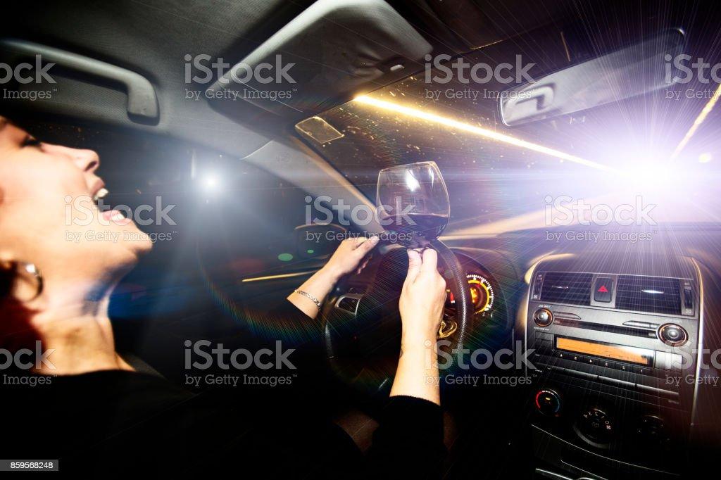 Conducteur d'un véhicule conduit une voiture tenant un verre de vin - Photo