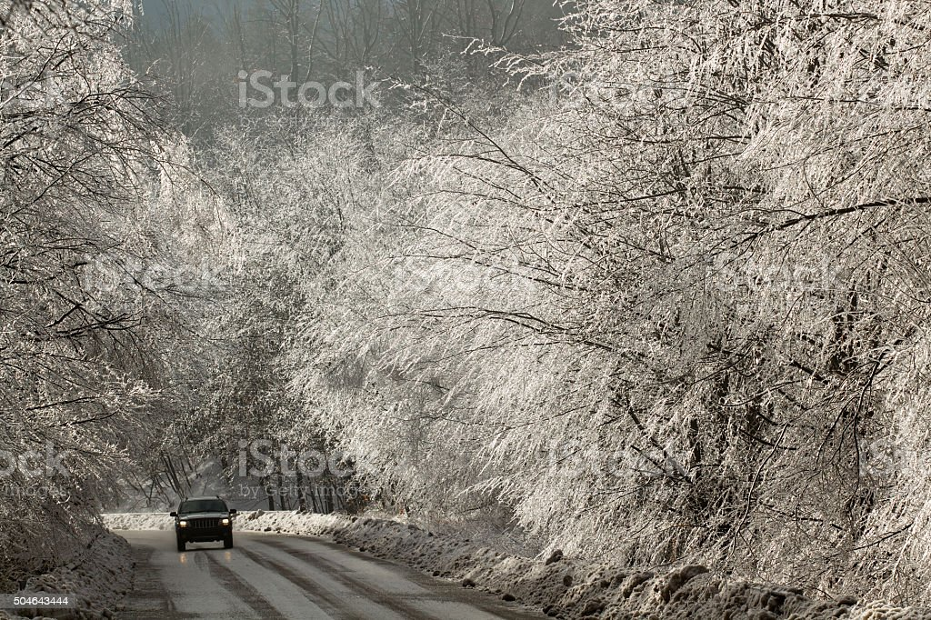 Motor vehicle passing down a mountain road in winter conditions stock photo