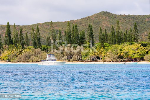 Motor yacht anchored off the Iles des Pines, New Caledonia, South Pacific.
