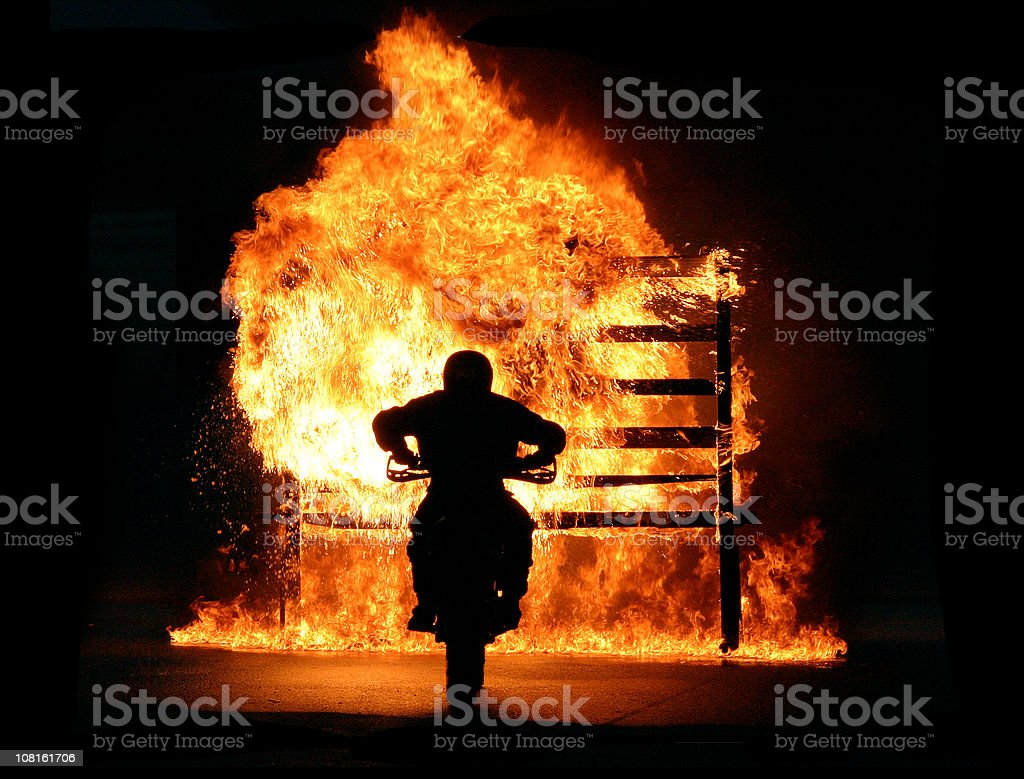 Motorbike driving through wall of fire stock photo