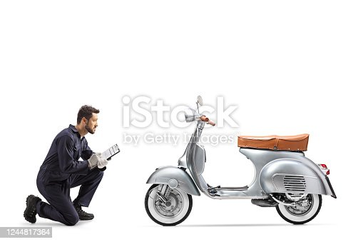 Motorbike mechanic checking a silver scooter and writing a document isolated on white background