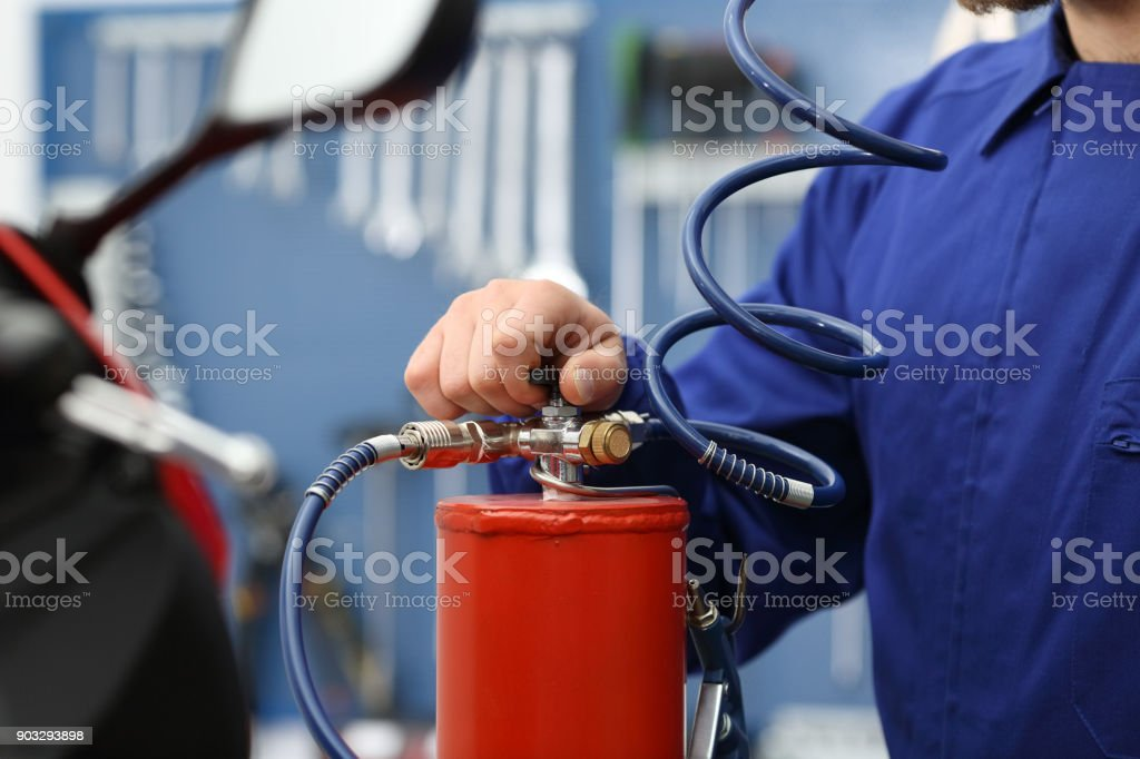 Motorbike mechanic hand using elevator stock photo