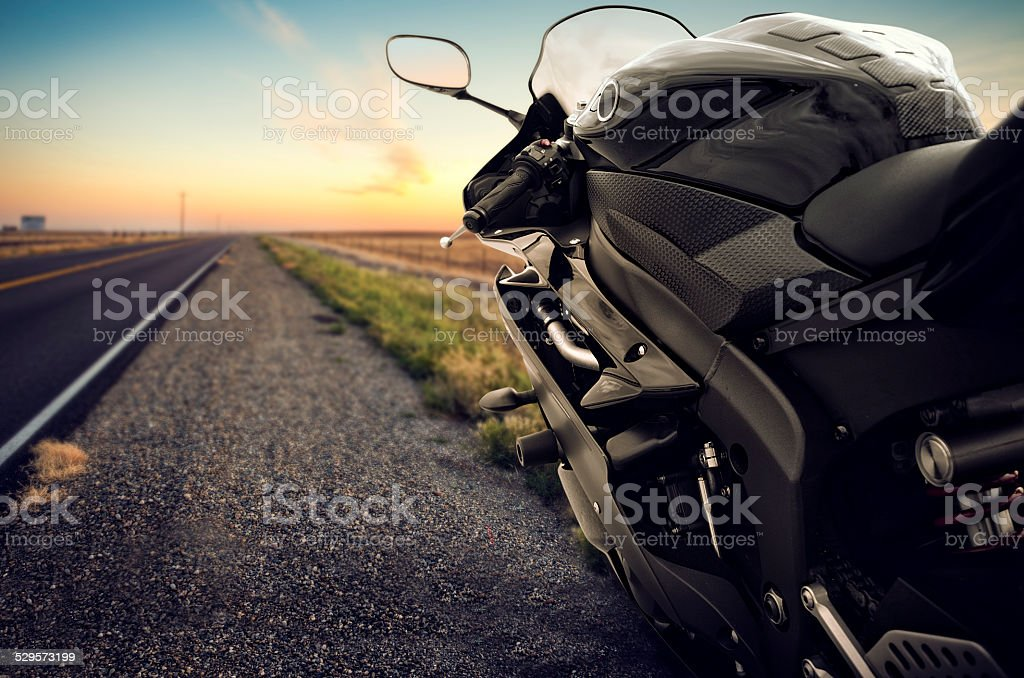Motorbike on an empty road at sunset stock photo