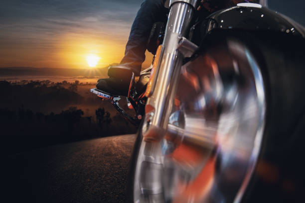 moto en la carretera de asfalto. divertirse conduciendo el camino vacío contra el amanecer en el fondo del bosque - foto de stock