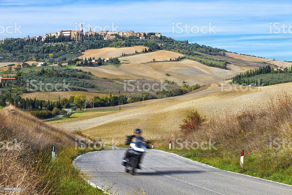 Motorbike on Winding Road, Pienza in Background, Tuscany, Italy royalty-free stock photo