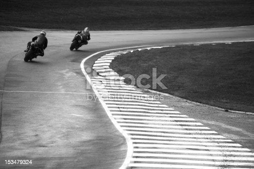 Motorbikes racing through a tight corner.