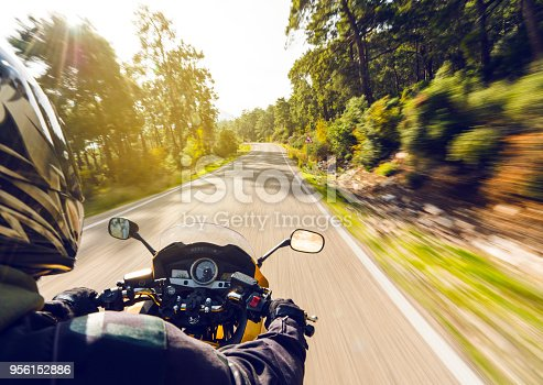 Motorcycle speeding down on an empty country road from over rider