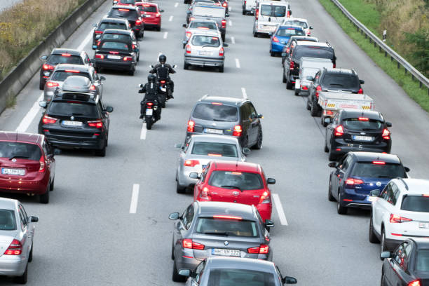 motorradfahrer überholen der fahrzeuge im stau - autos und motorräder stock-fotos und bilder