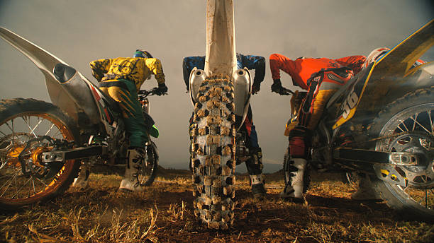 Motorbike riding Motocross riders at start of race. three wheel motorcycle stock pictures, royalty-free photos & images