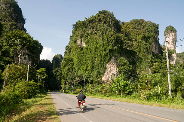 motorbike riding through karst rock formations near krabi in thailand - motorbike, umbrella stock pictures, royalty-free photos & images