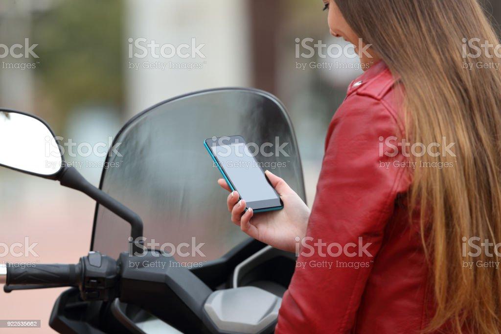 Motorbiker checking smart phone showing screen stock photo
