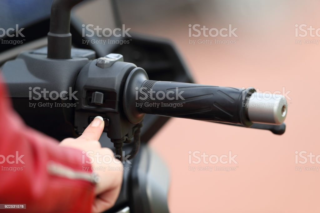 Motorbiker hand starting engine of a motorbike stock photo