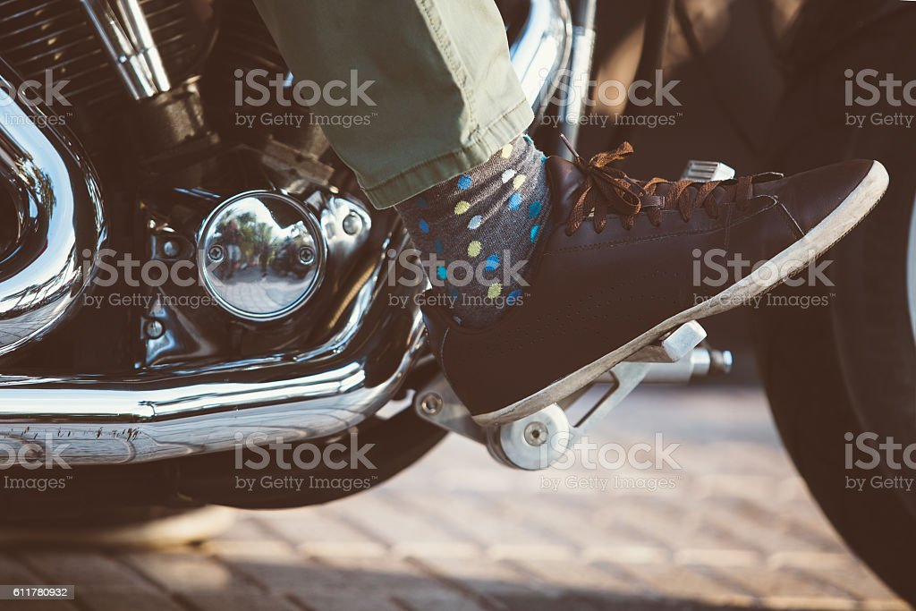 Motorbiker in leather shoe on throttle pedal stock photo