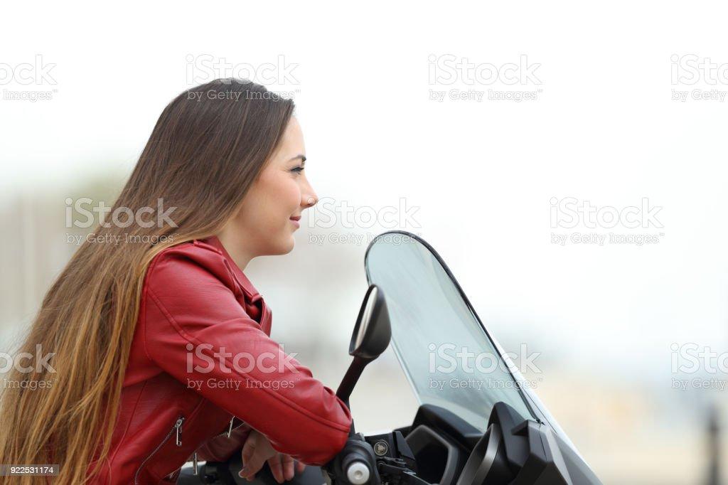 Motorbiker looking away on a motorbike stock photo