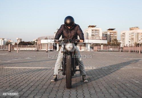 istock Motorbiker riding on motorbike in parking lot in city 497483992