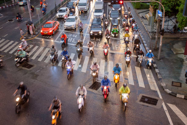 motorbikes at a busy junction in bangkok, thailand - motorbike, umbrella stock photos and pictures