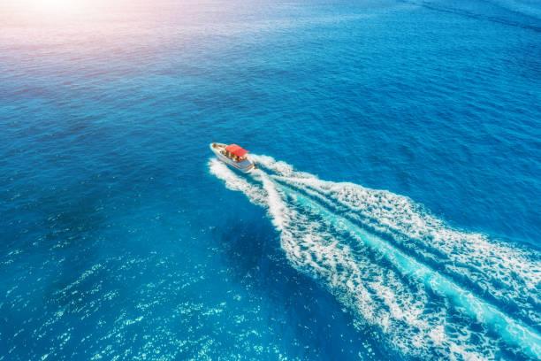 Motorboot am Meer in Balearen bei Sonnenuntergang. Luftaufnahme des Speed-Boot in kristallklarem blauen Wasser schweben. Sommerlandschaft. Draufsicht von Drohne. Seelandschaft mit Yacht in der Bucht in Bewegung. Tourismus – Foto