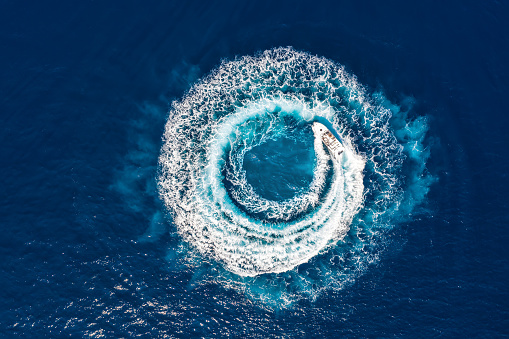 Motorboat forms a circle of waves and bubbles with its engines