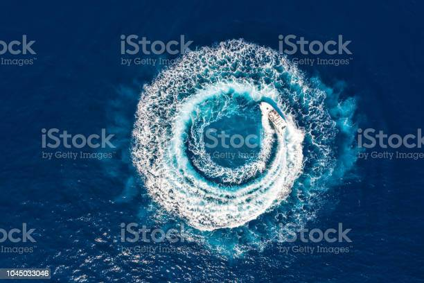 Photo of Motorboat forms a circle of waves and bubbles with its engines