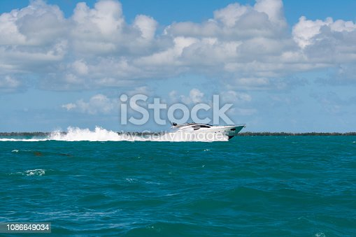 white luxury boat going fast over waves in florida keys