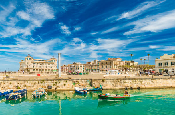 A motorboat sailing along the canal in Ortygia. Cityscape of the famous Sicilian town, Italy stock photo