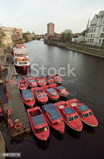 York, England - April 17, 2011: View from Station Road (Lendal Bridge) towards South East. 12 motorboats are moored in the river Ouse in York. One man is attending to them. The visible names of the boats are: Yvette, Ellen, Penny, Heather, Josephine, Lucy, Emma, Tina, Leonie, Alice-May.