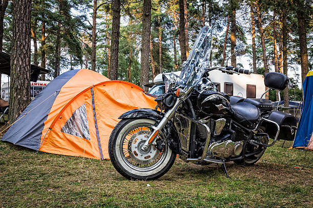 Motorcycle at the campsite Augustów, Poland - August 11, 2015:Morning view of custom black motorcycle stand at the campsite, Augustów, Poland  kawasaki heavy industries stock pictures, royalty-free photos & images
