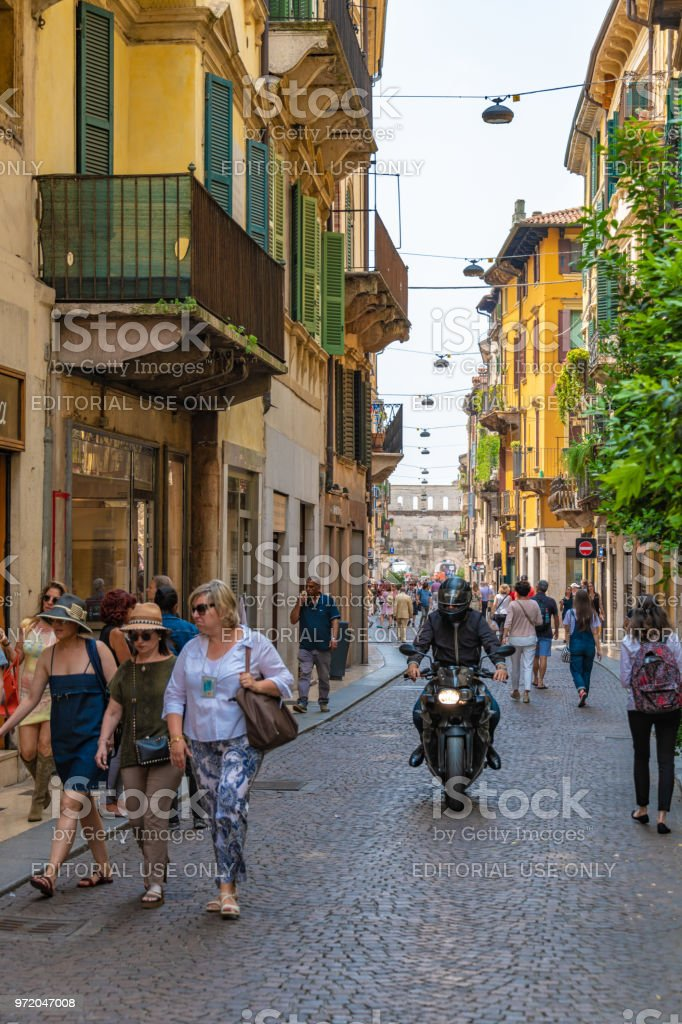 A motorcycle comes down a pedestrianised street in Verona, Italy stock photo